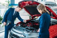 Kvinnliga och manliga försäljningschefer av en bilvisningslokal som ser under bilen Arkivfoton