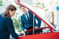 Kvinnliga och manliga försäljningschefer av en bilvisningslokal som ser under den öppna bilen Royaltyfria Bilder
