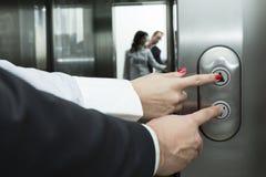 Kvinnliga och manliga pekfingrar som trycker på hissen, knäppas till olika riktningar Spegelreflexion av en lantbrukarhemingång Royaltyfri Bild