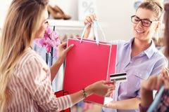 Kvinnliga påsar för kundhälerishopping i boutique royaltyfria foton