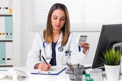 Kvinnliga pharmacis som skriver anmärkningar med askar av medicin i hand fotografering för bildbyråer