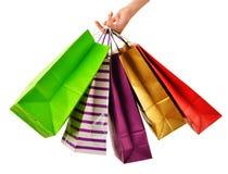 Kvinnliga påsar för shopping för handinnehavpapper som isoleras på vit Royaltyfri Fotografi