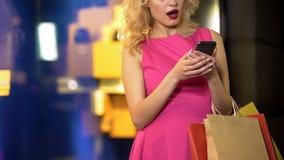 Kvinnliga shopaholic kontrollerande priser av hennes k?p p? online-diversehandel, mobil app royaltyfria bilder