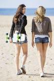 Kvinnliga skateboradåkare som går på stranden arkivfoto