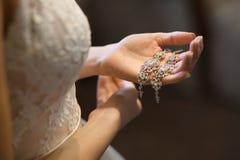 Kvinnliga skatter Halsband cirklar, örhänge i kvinnliga händer Fotografering för Bildbyråer