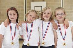 Kvinnliga skolasportar Team In Gym With Medals Arkivfoto