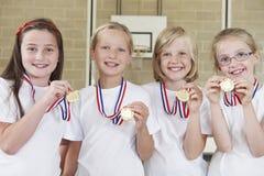 Kvinnliga skolasportar Team In Gym With Medals Arkivbild