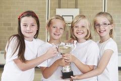 Kvinnliga skolasportar Team In Gym With Trophy Royaltyfri Bild