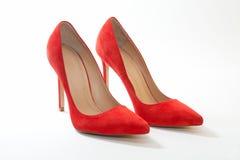 Kvinnliga skor som är ljusa, mockaskinn på vit bakgrund arkivfoto