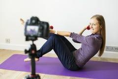Kvinnliga släkt TV-sändning för vloggerinspelning sportar hemma fotografering för bildbyråer