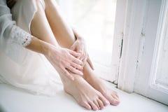 Kvinnliga sl?ta rakade ben st?nger sig upp applicera genomskinlig fernissa f?r omsorgshud royaltyfri bild