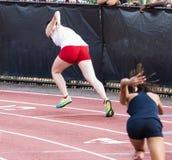 Kvinnliga sprinter som startar ett lopp på ett spår arkivfoton