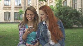 Kvinnliga studenter lyssnar till musik på smartphonen på universitetsområde arkivbild