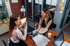 Kvinnliga studenter som arbetar på skolauppgift genom att använda bärbara datorer som sitter på skrivbordet i ett studierum royaltyfria bilder