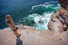 Kvinnliga tagande i havsikterna från klippaöverkantavsatsen på kusten royaltyfri fotografi