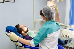 Kvinnliga tandläkare som arbetar på ung manlig patient Kontor för tandläkare` s Arkivfoton