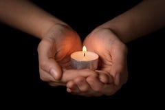 Kvinnliga tonåriga händer som rymmer den brinnande stearinljuset Fotografering för Bildbyråer