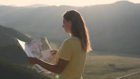 Kvinnliga turist- ställningar på kanten av en klippa med en översikt i hennes händer och söker efter en rutt för lopp stock video