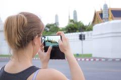 Kvinnliga turister rymmer en mobiltelefon, en smartphone som tar a arkivfoton