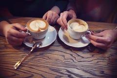 Kvinnliga vänhänder som rymmer koppar kaffe Fotografering för Bildbyråer
