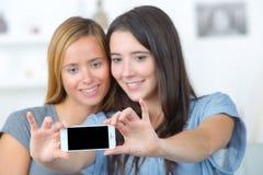 Kvinnliga vänner hemmastadda tagande Selfie genom att använda den smarta telefonen royaltyfria foton