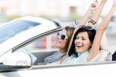 Kvinnliga vänner i bilen med händer upp arkivbilder
