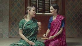 Kvinnliga vänner i sari som smakar den fragant indiska maträtten stock video