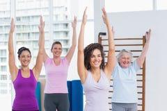 Kvinnliga vänner med armar lyftte att öva i idrottshall Arkivfoto
