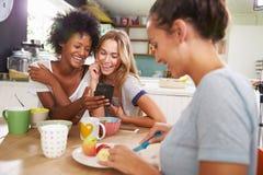 Kvinnliga vänner som äter frukoststunden som kontrollerar mobiltelefonen Royaltyfri Fotografi