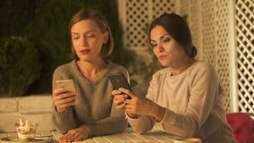 Kvinnliga vänner som bläddrar telefoner som försöker att finna foto som diskuterar att shoppa arkivfilmer