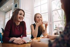 Kvinnliga vänner som dricker kaffe som har en angenäm konversation i en hemtrevlig romantisk restaurang royaltyfria foton