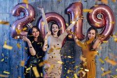 Kvinnliga vänner som firar att spela och att dansa Nytt år jul, xmas royaltyfri fotografi