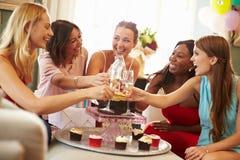 Kvinnliga vänner som gör ett rostat bröd för att fira födelsedag arkivfoto