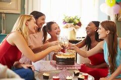 Kvinnliga vänner som gör ett rostat bröd för att fira födelsedag fotografering för bildbyråer