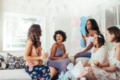 Kvinnliga vänner som har gyckel på baby shower Arkivbilder