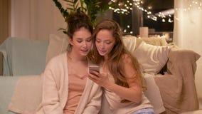 Kvinnliga vänner som hemma tar selfie vid smartphonen lager videofilmer
