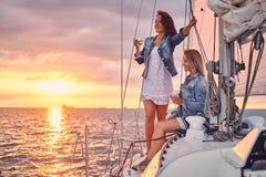 Kvinnliga vänner som kopplar av på yachten med exponeringsglas av vin i händerna, under solnedgång på sjögångarna royaltyfri bild