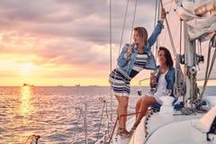 Kvinnliga vänner som kopplar av på yachten med exponeringsglas av vin i händerna, under solnedgång på sjögångarna royaltyfria bilder