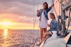 Kvinnliga vänner som kopplar av på yachten med exponeringsglas av vin i händerna, under solnedgång på sjögångarna arkivbild