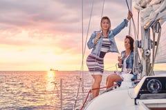 Kvinnliga vänner som kopplar av på yachten med exponeringsglas av vin i händerna, under solnedgång på sjögångarna royaltyfri foto