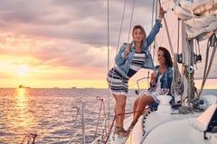 Kvinnliga vänner som kopplar av på yachten med exponeringsglas av vin i händerna, under solnedgång på sjögångarna royaltyfri fotografi