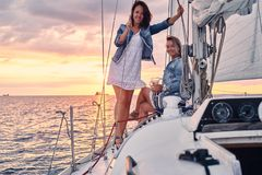 Kvinnliga vänner som kopplar av på yachten med exponeringsglas av vin i händerna, under solnedgång på sjögångarna fotografering för bildbyråer
