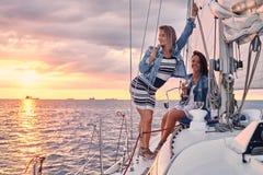 Kvinnliga vänner som kopplar av på yachten med exponeringsglas av vin i händerna, under solnedgång på sjögångarna arkivbilder