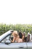 Kvinnliga vänner som läser översikten i cabriolet mot klar himmel Royaltyfria Foton