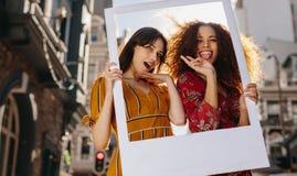 Kvinnliga vänner som poserar med en tom bildram royaltyfria foton