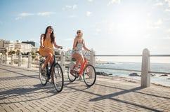 Kvinnliga vänner som rider deras cyklar på promenaden Arkivfoton
