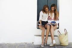 Kvinnliga vänner som sitter i dörröppningen som läser en resehandbok, Ibiza royaltyfri fotografi