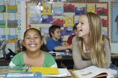 Kvinnliga vänner som skrattar i klassrumet arkivbild