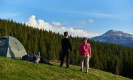 Kvinnliga vänner som tillsammans fotvandrar i bergen royaltyfri bild