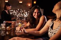 Kvinnliga vänner som ut tycker om natt på coctailstången royaltyfri foto